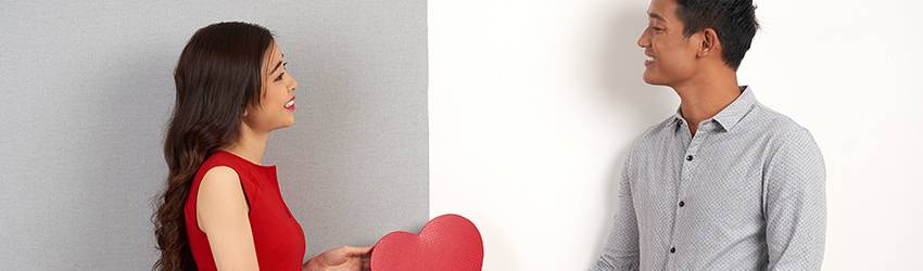 Two people stand next to each other on two differently painted walls (white on the right and grey on they left). The woman on the left hands the man on the right a red paper cutout heart.