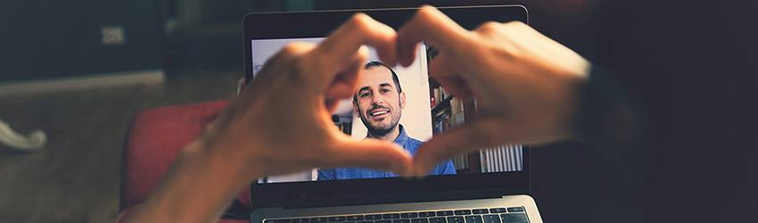 A person is making a heart with their hands at their partner who is on a video chat with them on their computer screen.