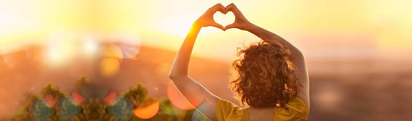A person holds their hands above their head in a heart shape in front of a setting Sun representing Leo.
