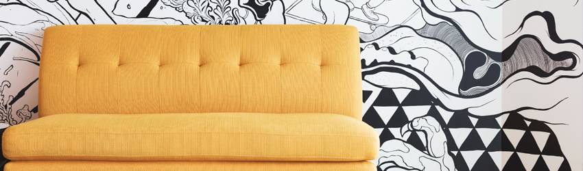 A yellow sofa on a black and white mural background.