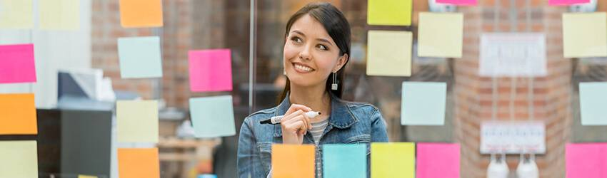 A woman brainstorms for her career while staring at a clear whiteboard covered in post it notes. She smiles and holds a marker.