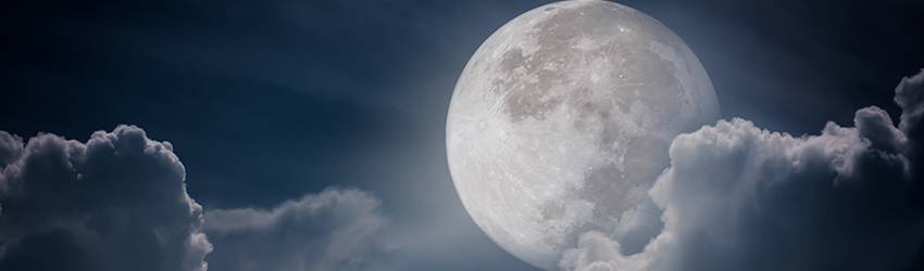 A Full Moon is partially obstructed by clouds.