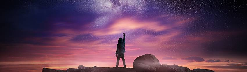A person stands under the stars, reaching up to the sky.