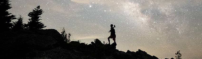 A person is climbing a hill in front of a grey colored starry sky.