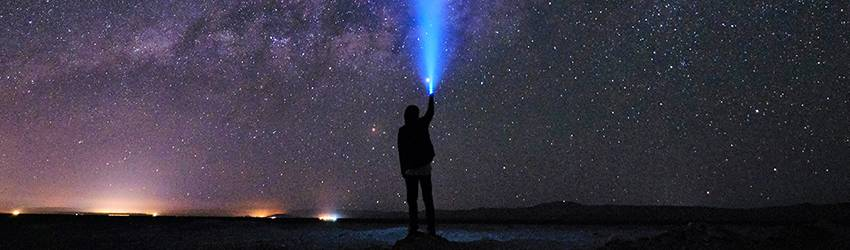 A woman points a flashlight directly above her into the purple star-filled sky.