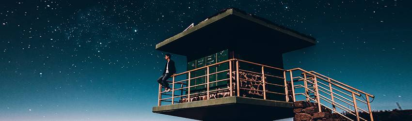 A person sitting on the railing of an observatory tower.