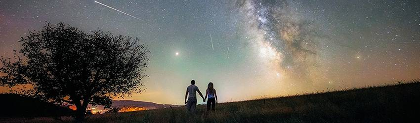 Two people holding hands are silhouetted as they walk towards a green and blue galaxy sky at sunset.
