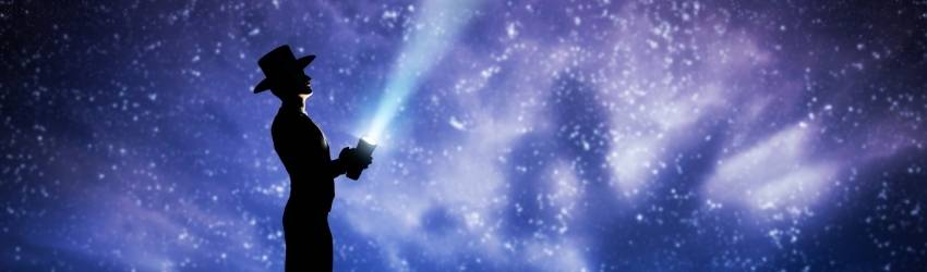 A shadowed figure stands, holding a flashlight up to the night sky. The expansive sky is illuminated by the white stars in shades of blue, purple, and black.