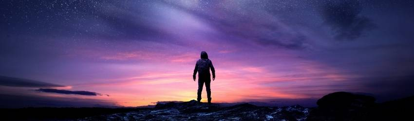 A shadowed figure stands amidst the background of the night sky in pink and purple hues.