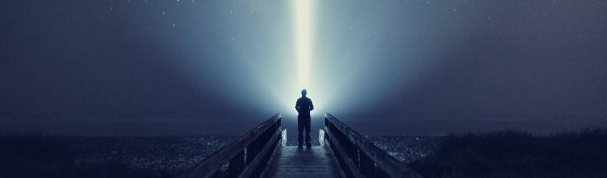 A figure stands against the night sky illuminated by a single strand of light.