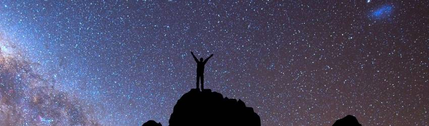 A shadowed figure stands on top of a cliff, facing the night sky.