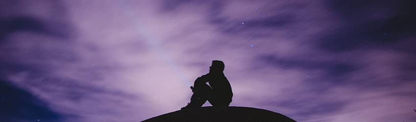 Man sitting on a mountain with purple stars behind him.