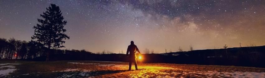 man holding lantern staring at the night sky