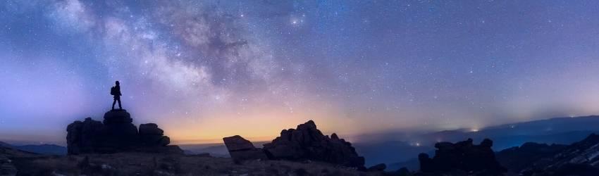 A shadowed figure looks over the starry sky.