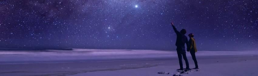 Two figures gaze upwards into the starry night sky.