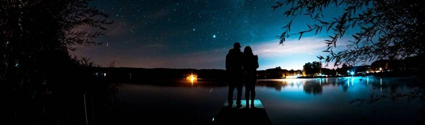 Two people stand holding each other and watching the stars.