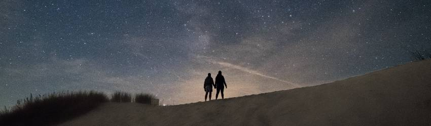Two silhouetted figures appear to be walking across a hill. The night sky is dark blue and peach and there is a shooting sky visible.
