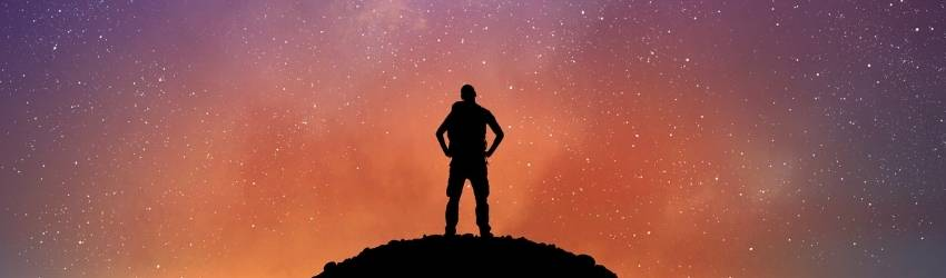 A shadowed figure stands on a cliff with their hands on their hips, facing the night sky lit up in hues of orange and yellow.
