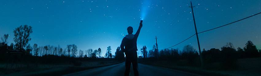 A person pointing a flashlight up at the stars against a blue night sky.