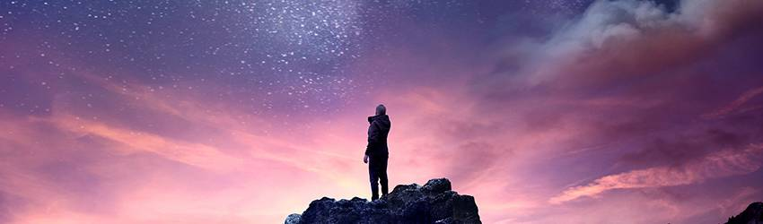 A man stands at the top of a mountain staring up at a purple galaxy sky.