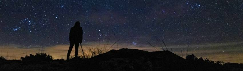 A man stands on a mountain looking at the sunrise. There are stars twinkling above him.