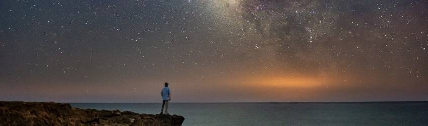 A person standing on a cliff next to the ocean stares up at the stars.