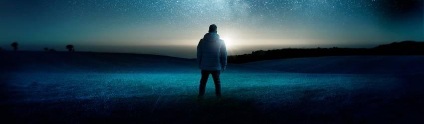 A man in winter gear stands under a navy blue night sky.