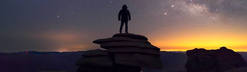 A man stands on the top of a hill looking up at the night sky.