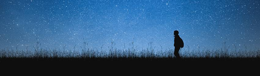 A silhouetted man is walking to the left of the frame along a path after dark. The sky is blue and full of stars.