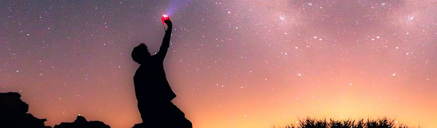 A person holds a red flare against a red starry sky.