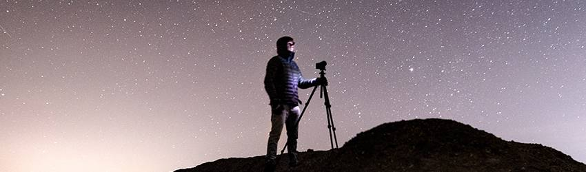 A person stands on a hill with a telescope with a purple starry sky behind them.