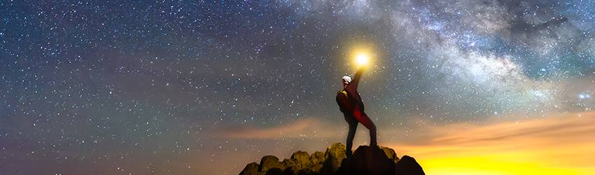 A man stands on a mountain stargazing and holding a glowing orb above himself.