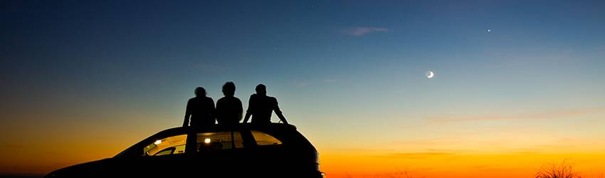 Three people sit on the roof of a car watching the sunset.