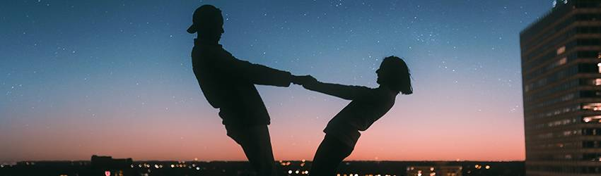 Two people dance in front of a blue and pink sunset. They are silhouettes against the sky.