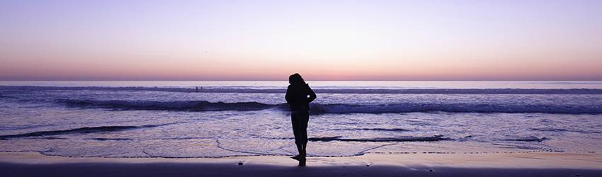 A person stands on a beach at sunset.