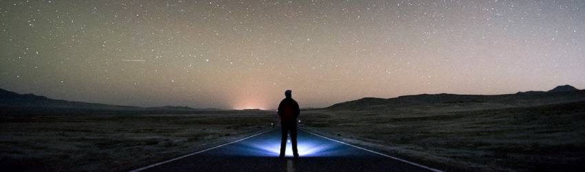A silhouetted person stands in front of a dark starry night.