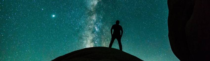 black figure standing in front of a blue galaxy of stars