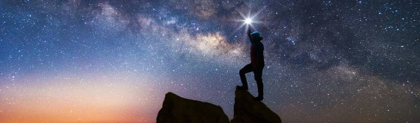A silhouetted figure stands on a cliff overlooking the night sky. It has shades of peach and blue in it and the stars are visible.