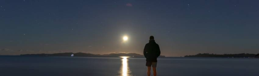 A man stands in front of a lake looking at the moon. It reflects off the water.