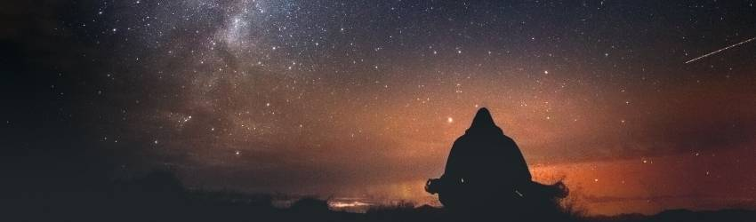 A person meditates against a galaxy sunset.