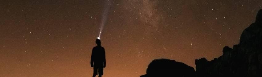 A man with a headlight stands under an orange starry sky.