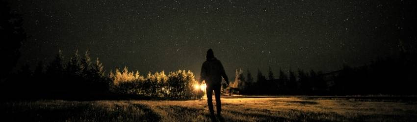 A dark shadowed figure walks towards the viewer with a starry sky above.