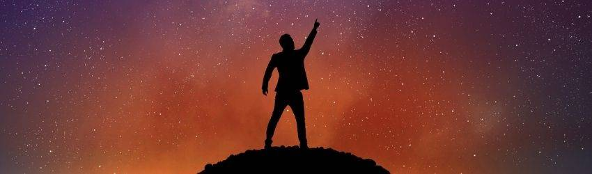 A silhouetted figure raises their hand to the sky, pointing at what appears to be a meteor flying throught the night sky. The stars are visible in the purple and orange sky.