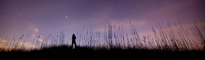A man walks across a field in the distance against a purple starry night sky.