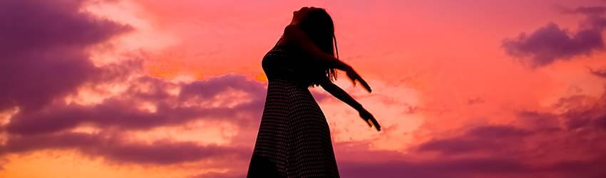 Woman's silhouette in front of a pink sky. She is on a hill and tilting her head backwards.