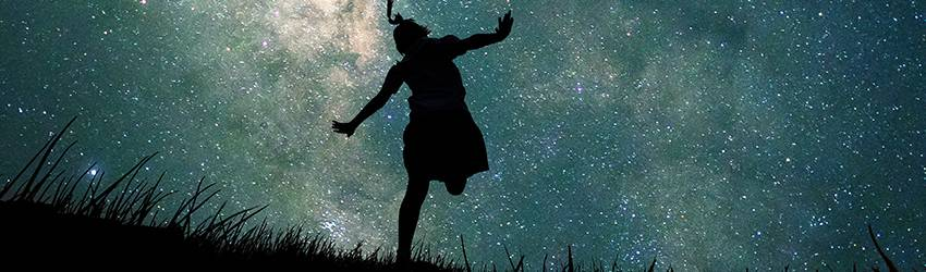 Woman pretending to fly on a hill in front of the stars.