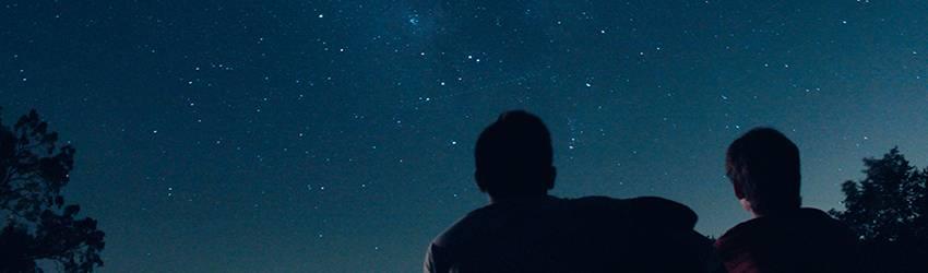 Two people stargaze together on a dark blue star-filled sky.