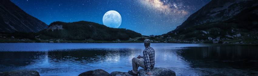 A man sits on a rock looking at the Full Moon next to a lake.