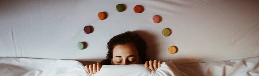 Person sleeping with chakra stones above their head.