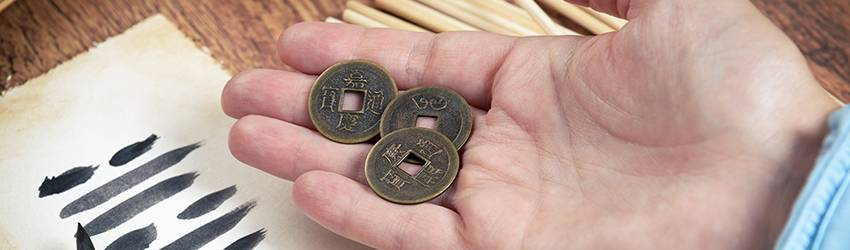 A man holds the coins used in I Ching divination.